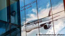 A large Qatar Airways graphic being viewed by a woman from a Cairo office bureau
