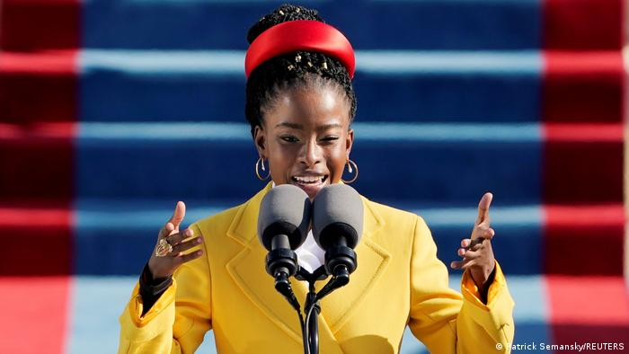 Amanda Gorman, a woman in a bright yellow jacket speaks at a microphone