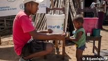 A member of the NGO Action Contre la Faim gives drinking water to an infant during a malnutrition screening session in the Municipality of Ifotaka, in southern Madagascar, on December 14, 2018. - In the village of Ifotaka, at the southern tip of Madagascar, the noise and excitement of the country's election campaign seems far away as locals confront more pressing needs in a daily struggle for food. For several seasons now, the entire southern part of Madagascar has been caught up in a drought that has made water increasingly scarce, wrecking even efforts to grow rice -- the staple food. (Photo by RIJASOLO / AFP)