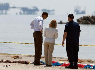 President Barack Obama, looks at booms laid out to collect oil