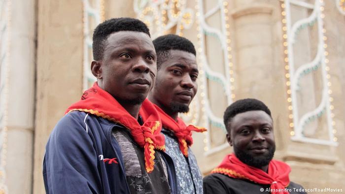 Filmstill aus A Black Jesus: drei junge Männer mit rot-gelben Halstüchern