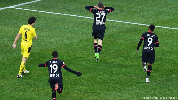 Florian Wirtz runs off to celebrate his winning goal, followed closely by Leon BAiley and Moussa Diaby
