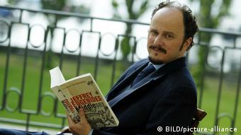 Pulitzer-Preisträger Jeffrey Eugenides sitzt auf einem Balkon und hält seinen Roman Middlesex aufgeschlagen in der Hand