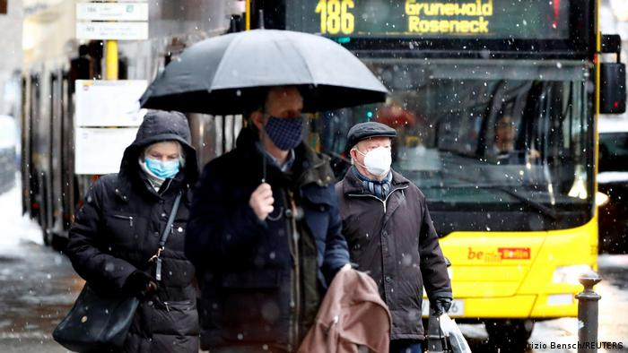 People wear face masks as they walk past a bus during lockdown