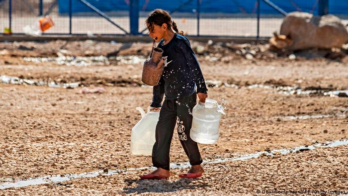 A girl carries water containers after water outages in the Al-Hasakah region in north east Syria