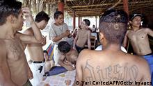 LA LIBERTAD, EL SALVADOR: Members of the Mara 18 youth gang - under a rehabilitation process with the Bautista de Avivamiento church, listen to rehabilitated Cri-Cri (3-L), who reads them the menu at Conchalio beach in La Libertad, El Salvador, 23 March 2005. Cri-Cri, a former member of the gang, now works as a waiter and is known as Christ's Angel, after his rehabilitation with the Catholic Chuch. Violence from street gangs, known in the region as maras, are considered the most pressing security issues in large cities in El Salvador, Guatemala and Honduras - countries which will take part in the Anti-Maras Meeting on April 1st, in Tegucigalpa. AFP PHOTO/Yuri CORTEZ (Photo credit should read YURI CORTEZ/AFP via Getty Images)
