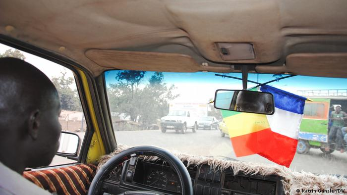 Taxi driver with French and Malian flags hanging at the windshield