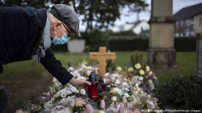 In this photo illustration a man puts a grave light on a grave while wearing a face mask