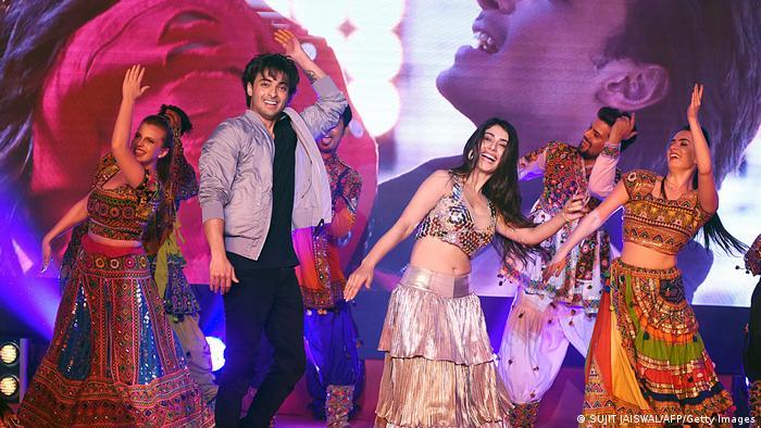 Männer und Frauen in bunten Kostümen tanzen auf einer Bühne in einem Bollywoodfilm.