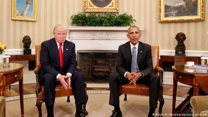 Donald Trump und Barack Obama sitzen im Oval Office und blicken in die Kamera.