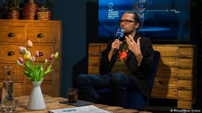 Oliver Baumgarten, künstlerischer Leiter des Max Ophüls Preises, mit Mikrofon im Studio