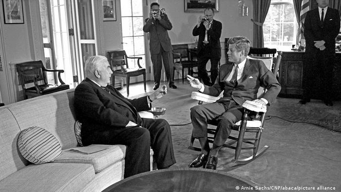 John F. Kennedy sitzt in einem Rollstuhl im Oval Office und spricht mit dem Premierminister von Australien, Robert Menzies.