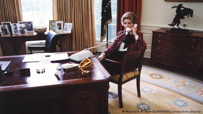 Nancy Reagan sitzt am Schreibtisch des Oval Office und telefoniert.