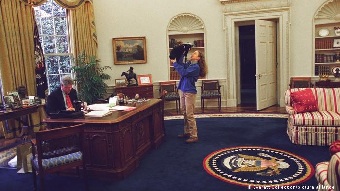 Bill Clinton sitzt am Schreibtisch, während seine Tochter Chelsea im Oval Office mit ihrem Hund spielt.