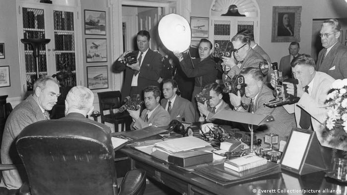 Schwarzweißfoto zeigt das Oval Office zu Zeiten von Harry S. Truman, der auf einem alten Lederdrehstuhl sitzt. Er ist umgeben von Journalisten mit Kameras.