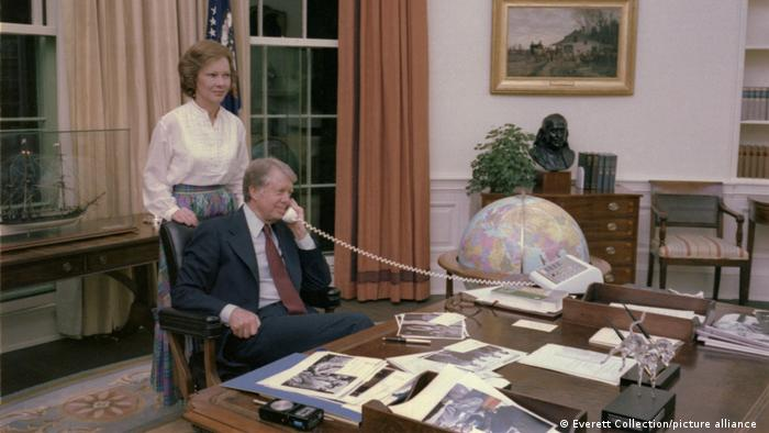 Präsident Jimmy Carter sitzt am Schreibtisch im Oval Office und telefoniert. Hinter ihm steht seine Ehefrau Rosalynn Carter.