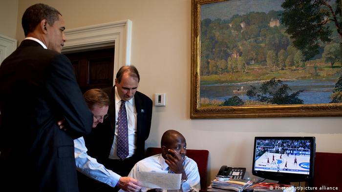 Barack Obama steht vor einem Monitor und sieht ein Basketballspiel an.
