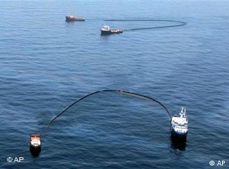Skimming vessels collect oil near the source of the Deepwater Horizon oil spill in the Gulf of Mexico in May 2010
