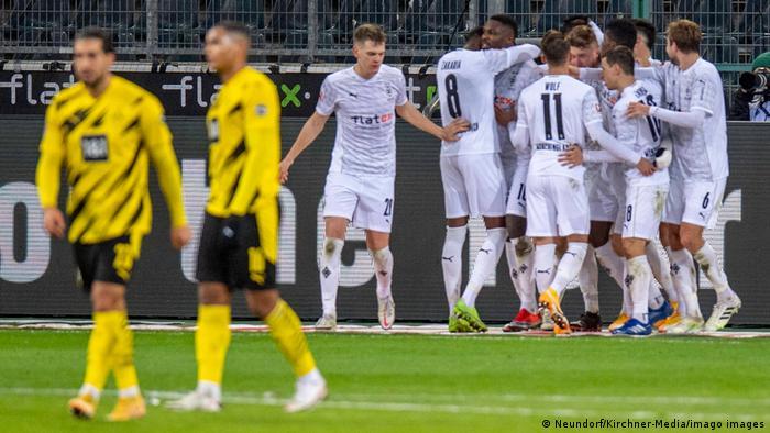 Borussia Mönchelgladbach players celebrate with dispondent Borussia Dortmund players in the foreground