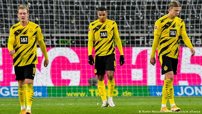 Borussia Dortmund's Julian Brandt, Manuel Akanji and Erling Haaland look crestfallen.