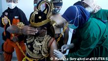 An Indonesian health care worker injects a dose of Sinovac's vaccine to a man dressed in Indonesia's traditional human puppet costume
