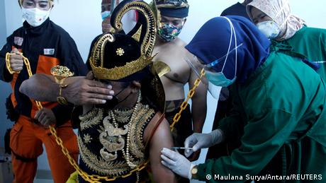 An Indonesian health care worker injects a dose of Sinovac's vaccine to a man dressed in Indonesia's traditional human puppet costume known as 'Wayang