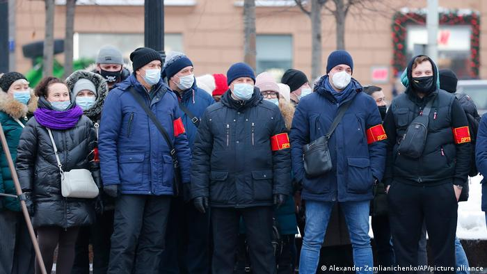 A group of vigilantes in blue coats wait to block a street. They are wearing red arm bands.