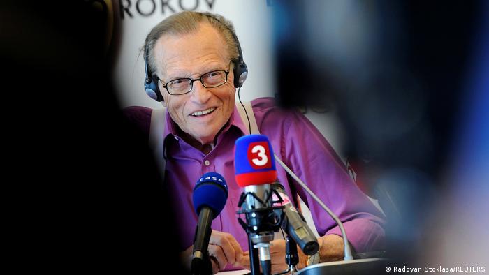 Larry, com fones de ouvido e camisa roxa, fala em vários microfones. Parece ser um estúdio.