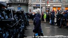 A woman stands in front of Russian riot police