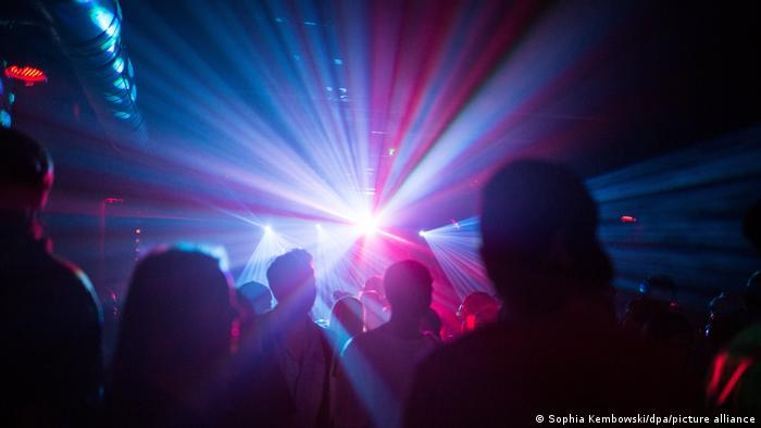 Clubbers dance in a darkened dance club with blue and purple lights