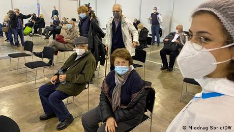 People sitting in a vaccination center in Belgrade