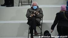 Encolhido de frio numa cadeira isolada, o senador americano Bernie Sanders assiste à cerimônia de posse do presidente Joe Biden em Washington, DC, 20 de janeiro de 2021.