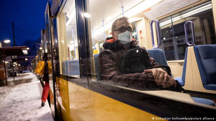A man wearing a protective mask sits in a tram car