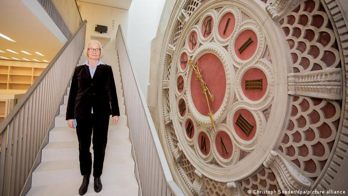 Huge clock alongside a staircase, with Barbara Schneider-Kempf, director general of Berlin's public library, standing on the stairs