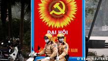 Police officers patrol near a poster in Hanoi for the 13th national congress of the Communist Party of Vietnam