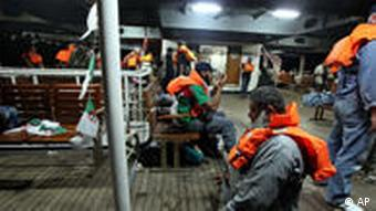 Activists wearing life vests pray and wait on board the Mavi Marmara