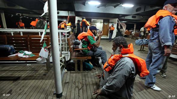 Activists wearing life vests pray and wait on board the Mavi Marmara