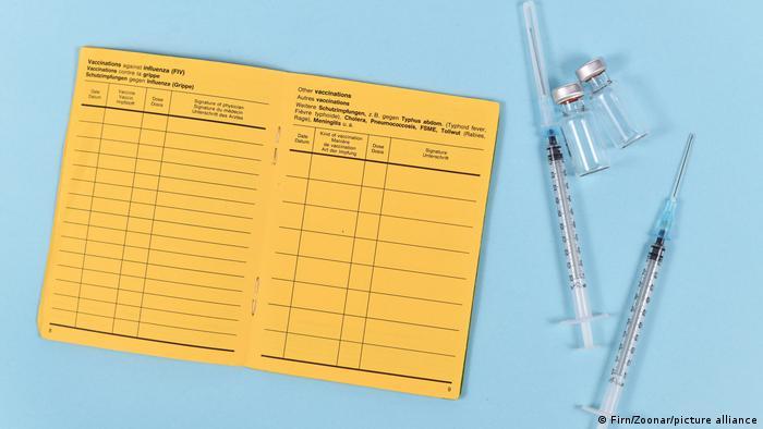 Carteira de vacinação ao lado de duas seringas.