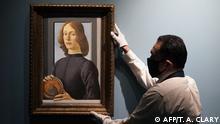 Ein Mann mit Schutzmaske und Handschuhen hängt das Porträt des Jungen Mannes mit Medaillon von Sandro Botticelli auf
