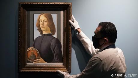 Man holds painting Young Man Holding a Roundel up on a wall