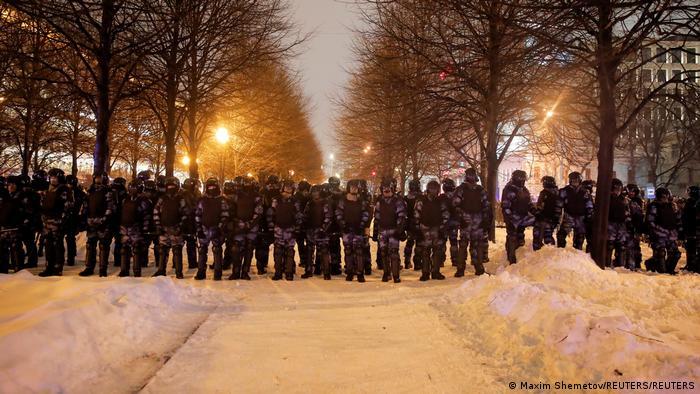 Fileira de policiais de roupa de camuflagem em rua nevada e arborizada