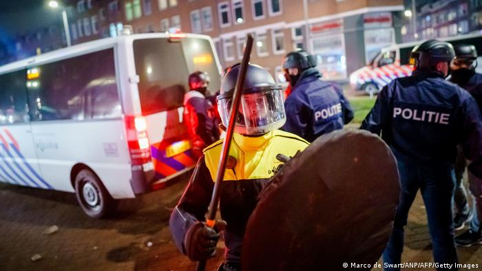 A policeman with helmet and shield holds a baton as he stands next to a police van on Beijerlandselaan in Rotterdam