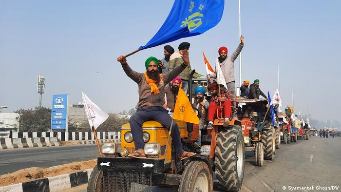 Tractors carrying protesters waving flags