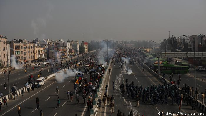 Clouds of tear gas rise up among crowds of protesters who are making their way along major roads in the capital