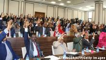 23.09.2020 Somali members of Parliament raise their hands to approve the new Somali Prime Minister Mohamed Hussein Roble, a Swedish-trained civil engineer, in Mogadishu, Somalia, on September 23, 2020. (Photo by STRINGER / AFP) (Photo by STRINGER/AFP via Getty Images)