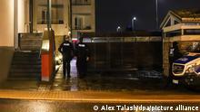 Bei einer Razzia im nordrhein-westfälischen Herdecke stehen Polizeibeamte vor der Einfahrt zu einem Hof.