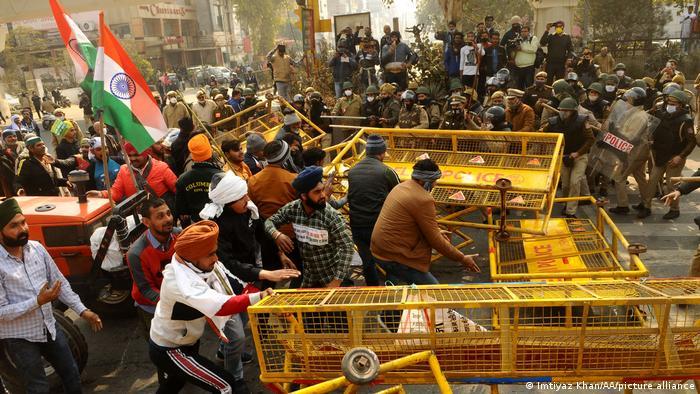 Bauer in Indien stürmen von der Polizei errichtete Barrikaden, mit Schilden und Helmen ausgerüstete Sicherheitskräfte weichen vor den Angreifern zurück