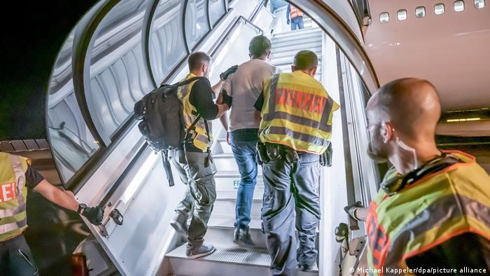 Police officers accompany an Afghanm man up plane steps