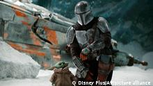 This image released by Disney Plus shows Pedro Pascal, as Din Djarin, right, with The Child, in a scene from The Mandalorian, premiering its second season on Friday. (Disney Plus via AP)