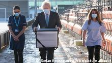 UK PM Boris Johnson carrying a box of AstraZeneca's COVID-19 vaccine
